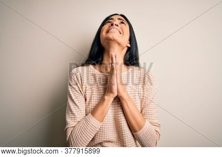 Young beautiful hispanic woman wearing elegant pink sweater over isolated background begging and praying with hands together with hope expression on face very emotional and worried. Begging.