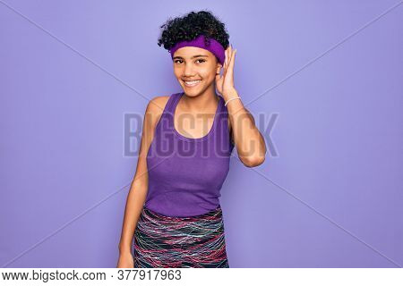 Beautiful african american afro woman wearing casual sportswear over purple background smiling with hand over ear listening an hearing to rumor or gossip. Deafness concept.