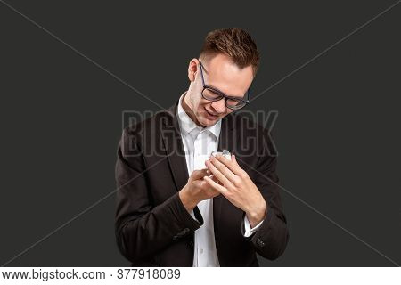 Special Gift. Birthday Present. Curious Business Man Opening Jewelry Box Smiling Isolated On Black.