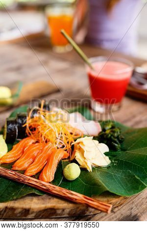 Japanese cuisine delicious sushi rolls and fresh sashimi served on a green leaf at restaurant