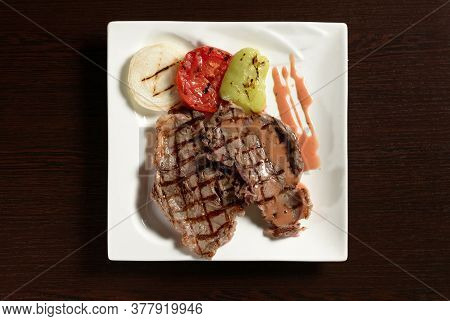 Roasted Beef Tenderloin With Grilled Vegetables Of Tomato, Onion And Bell Pepper On A Square Plate O