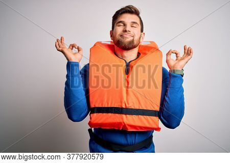 Young blond tourist man with beard and blue eyes wearing lifejacket over white background relax and smiling with eyes closed doing meditation gesture with fingers. Yoga concept.