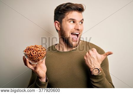 Young blond German man with beard and blue eyes holding bowl with baked pretzel pointing and showing with thumb up to the side with happy face smiling