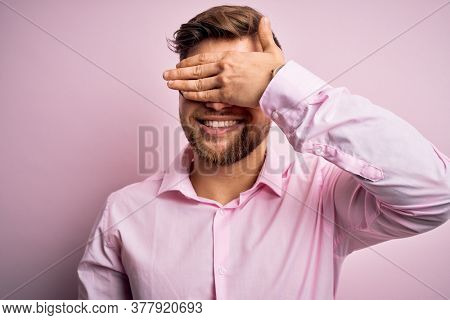 Young handsome blond man with beard and blue eyes wearing pink shirt and glasses smiling and laughing with hand on face covering eyes for surprise. Blind concept.