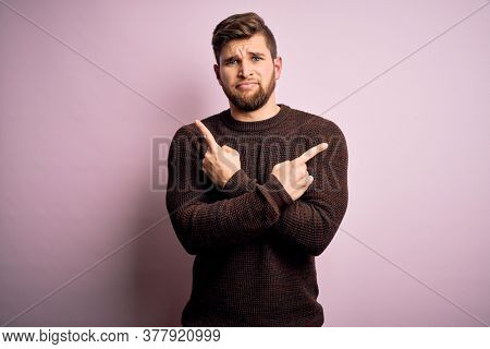Young blond man with beard and blue eyes wearing casual sweater over pink background Pointing to both sides with fingers, different direction disagree
