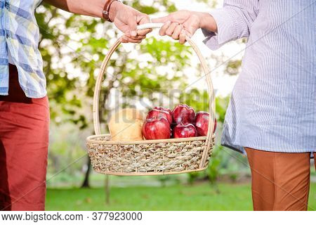 Elderly Asian Couple Walking Together And Carrying Fruit Baskets In A Public Park Enjoy Life After R
