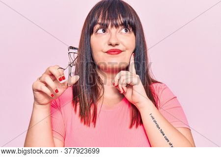Young plus size woman holding eyelash curler serious face thinking about question with hand on chin, thoughtful about confusing idea
