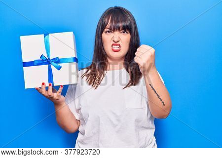 Young plus size woman holding gift annoyed and frustrated shouting with anger, yelling crazy with anger and hand raised