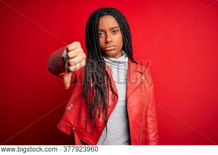Young african american woman wearing cool fashion leather jacket over red isolated background looking unhappy and angry showing rejection and negative with thumbs down gesture. Bad expression.