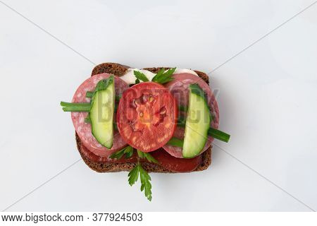 On The Table Is An Appetizing Sandwich With Sausage, Pomadom, Cucumber. The Sandwich Is Watered With