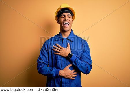 Young handsome african american worker man wearing blue uniform and security helmet smiling and laughing hard out loud because funny crazy joke with hands on body.