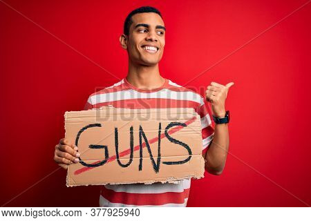 Young handsome african american man holding banner with prohibited guns message pointing and showing with thumb up to the side with happy face smiling