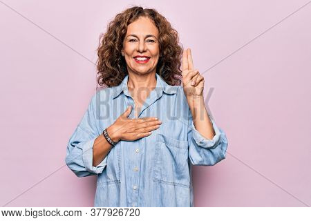 Middle age beautiful woman wearing casual denim shirt standing over pink background smiling swearing with hand on chest and fingers up, making a loyalty promise oath