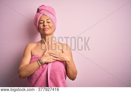 Middle age woman wearing bath towel from beauty body care over pink background smiling with hands on chest with closed eyes and grateful gesture on face. Health concept.