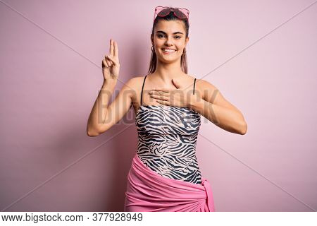 Young beautiful brunette woman on vacation wearing swimsuit over pink background smiling swearing with hand on chest and fingers up, making a loyalty promise oath
