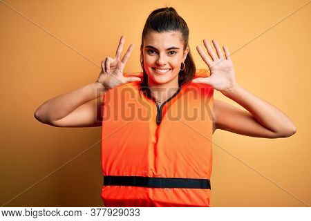 Young beautiful brunette woman wearing orange safe lifejacket over yellow background showing and pointing up with fingers number eight while smiling confident and happy.