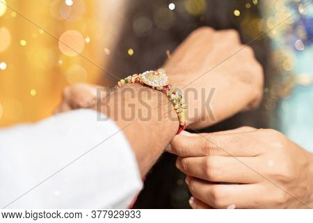 Closeup Of Hands, Sister Tying Rakhi, Raksha Bandhan To Brothers Wrist During Festival Or Ceremony -
