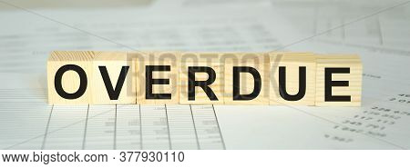 Text Overdue Written On Cubes And Financial Statements. Financing