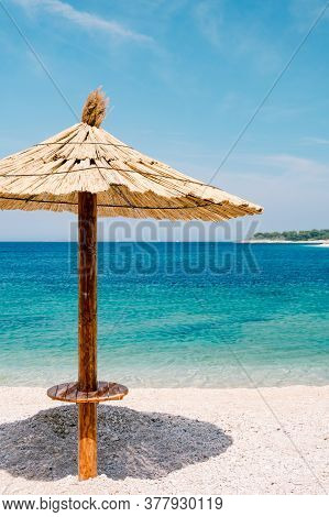 A Beach Thatched Umbrella Against The Blue Sky And Azure Water On A Sandy Beach In Croatia, In The C