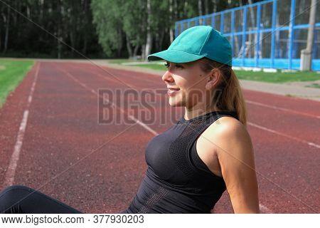 Happy Modern Woman Resting After Workout Or Running. Open Air Stadium. Outdoors Training. Woman Sitt