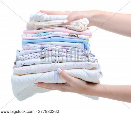 Stack Folded Baby Clothes In Hand On White Background Isolation