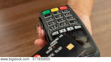 Payment Machine, Pos Terminal And Credit Card On Wooden Background.