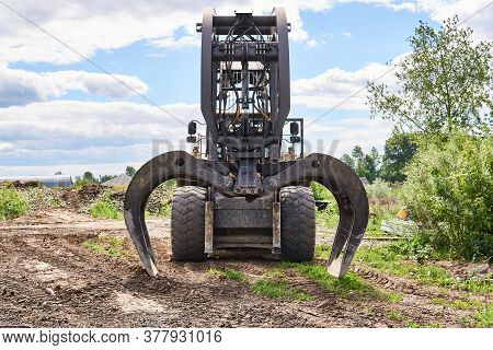 Modern Dual Function Grapple Skidder Stands On The Ground Outdoors