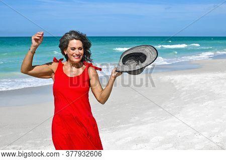 Beautiful Mature Woman Wearing A Red Summer Dress On The Beach