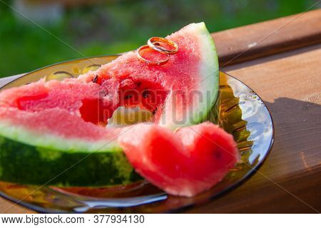 Two Rings Is A Symbol Of Love. Two Golden Wedding Rings On A Piece Of Watermelon. Beautiful Juicy Wa