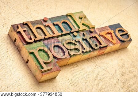 Think positive - word abstract in vintage letterpress wood type blocks against textured handmade paper, optimism, positivity and mindset concept