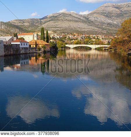 Beautiful Autumn View Of Trebisnjica River And Trebinje City. White Clouds Reflected In Water. Bosni
