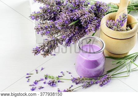 Bouquet Of Lavender Flowers, Wood Mortar With Pestle And Lavender Candle On The White Background Clo