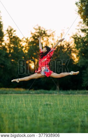 Japanese Ballerina In Red Kimono Jumps And Performs Gymnastic Twine On Lawn Background.