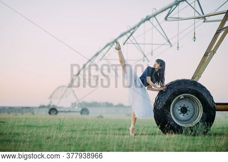 Japanese Ballerina In White Skirt Performs Gymnastic Twine In Field On Farm Near The Wheel Of Agricu