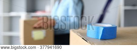 Close-up Of Cardboard Box With Blue Scotch On Top. Woman Carrying Package With Personal Stuff. Deliv