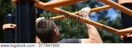Portrait Of Man Working Out On Sports Ground. Sportsman Pulling Up On Horizontal Bar On Athletic Fie