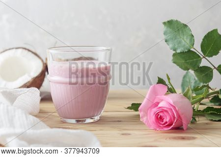A Glass Of Moon Milk With A Rose On A Wooden Table. Ayurvedic Relaxing Drink For The Night.