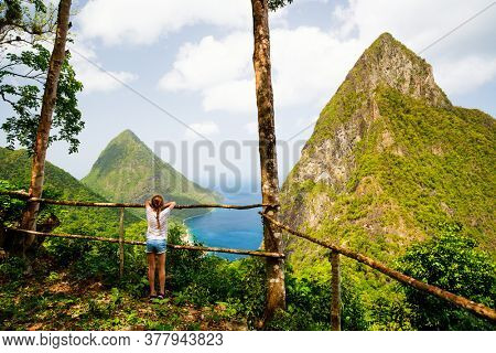 Back view of little girl enjoying scenery of Piton mountains on St Lucia island in Caribbean