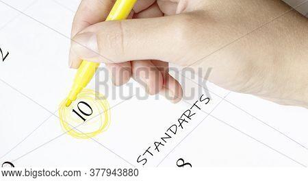 Hand Encircles A Date On A Calendar With Text Standarts Yellow Felt-tip Pen