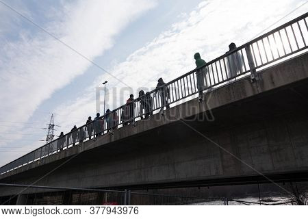 Spectators At An Event, People On A Bridge Walking To Venue