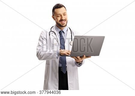 Male doctor standing and working on a laptop isolated on white background