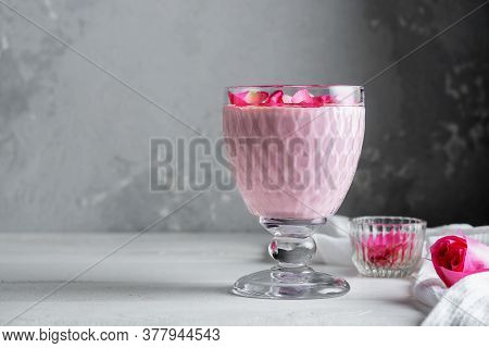 A Glass Of Moon Milk With A Rose On A White Table. Ayurvedic Relaxing Drink For The Night.