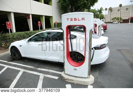 Santa Ana, California / USA - July 23, 2020: Tesla Electric Car Charging Station in a Shopping Mall Parking Lot. Tesla brand Electric Cars are being charged with electricity at a Charging Station.