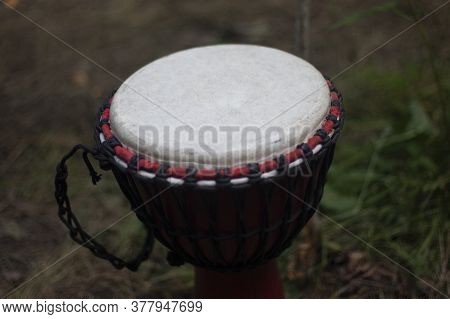 African Drum. Dark Frame With A Drum Standing Outside In The Forest. Musical Instrument For Playing
