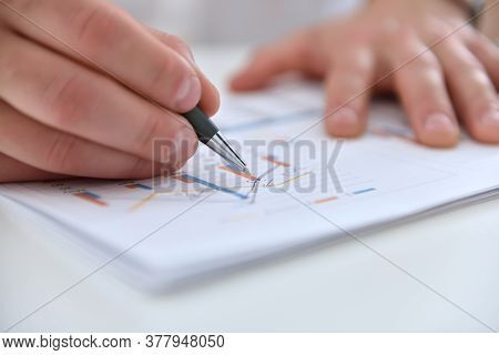 Businessman Hands Analyzing Financial Report And Statistics. Business And Financial Success Concept.