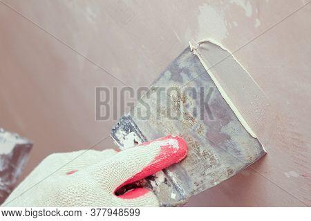 Puttying, Sealing Cracks With Gypsum Plaster Using A Spatula. Damaged Wall Repair.