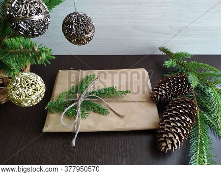 A Christmas Gift Wrapped In Craft Paper And Tied With Linen Thread Next To Fir Branches With Fir-con