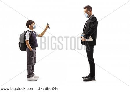 Full length profile shot of a schoolboy wearing a protective face mask and showing a mobile phone to a teacher isolated on white background
