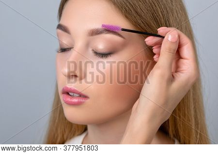 Make-up Artist Combing Eyebrows With A Brush To A Beautiful Young Blonde Teen Girl With Long Hair, M