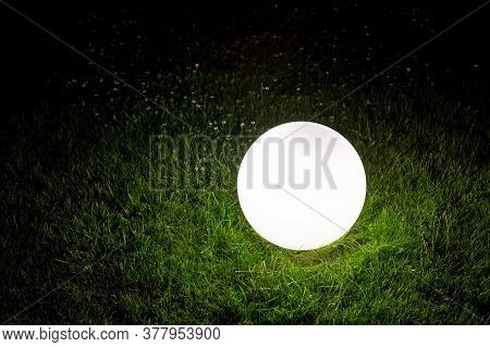 Illuminating Conglobate Ground Garden Lamp Of White Color Lies On A Green Lawn In Grass In The Backy